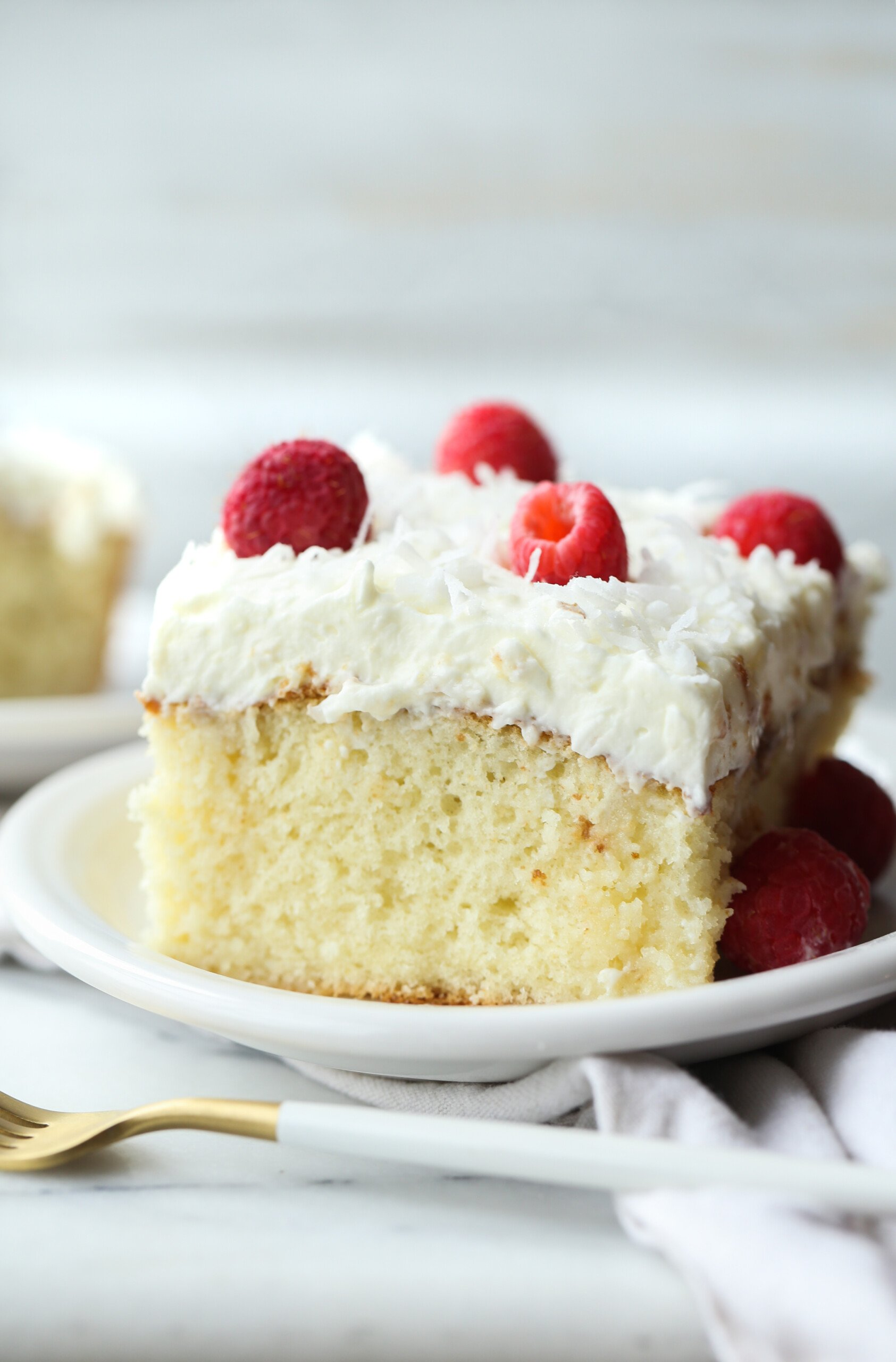 Slice of Coconut Poke Cake on a plate topped with whipped frosting