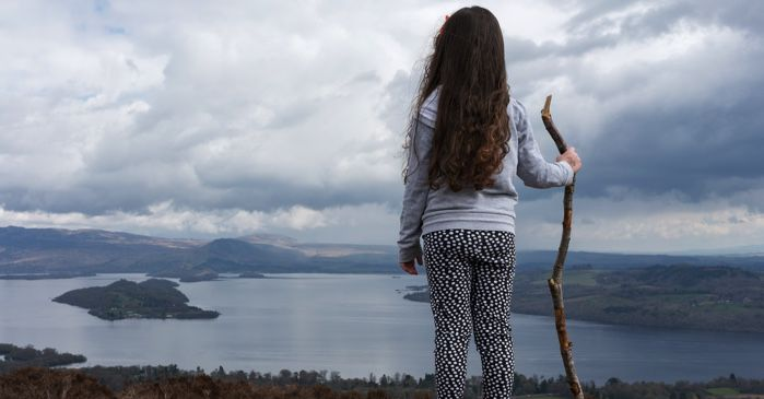 little girl standing on a hilltop overlooking the ocean with a walking stick for survivalist outdoors nature feature